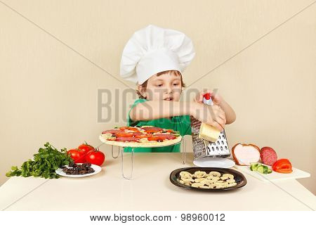 Little funny boy in chefs hat rubs on grater cheese for pizza