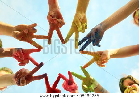 Hands of young people with Indian dyes on Holi color festival on blue sky background
