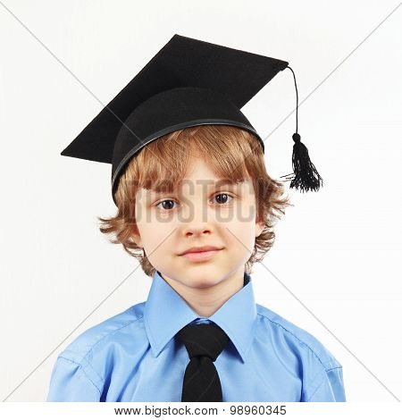 Little serious boy in academic hat on white background