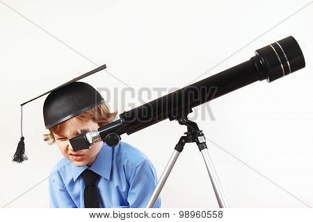 Little boy in academic hat looking through a telescope on white background