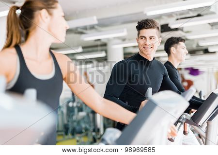 Handsome Man And Beautiful Young Woman Using A Stepper In A Gym