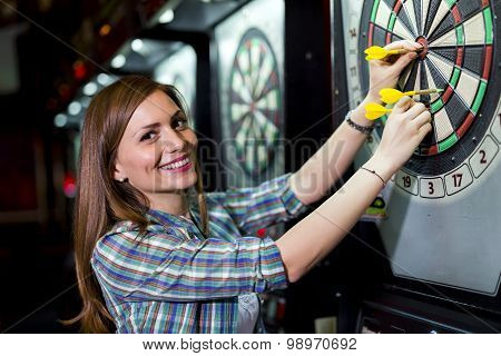 Young Beautiful Woman Playing Darts In A Club