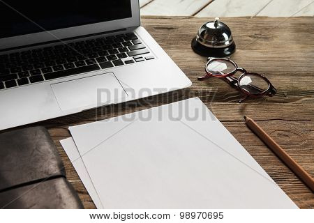 The laptop, blank paper, glasses and small bell on the wooden table