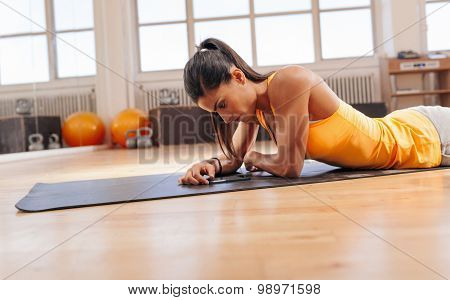 Woman Using Smart Phone After Workout At Gym