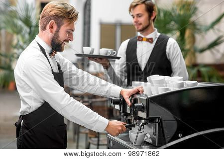 Barista making coffee with waiter