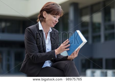 Businesswoman Checking The Spine Of A Book