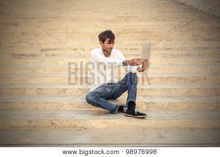 Man doing a selfie using a tablet