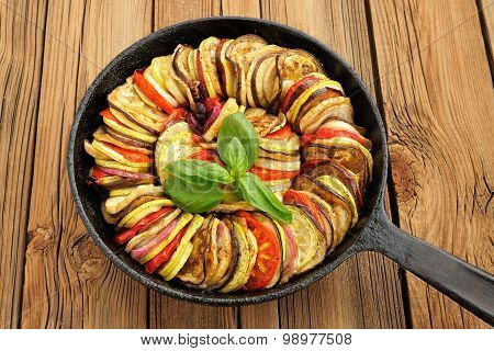 Tasty Vegetarian Ratatouille Made Of Eggplants, Squash, Tomatoes And Onions In Black Cast Iron Pan O