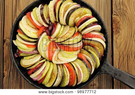 Raw Vegetables Layed For Ratatouille Made Of Eggplants, Squash, Tomatoes And Onions In Black Cast Ir