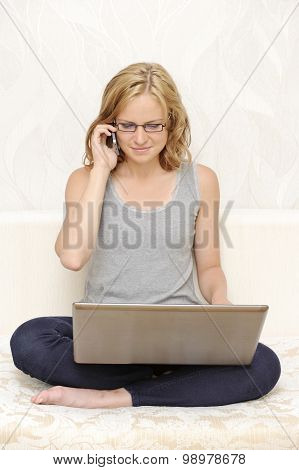 Young woman with a laptop talking on the phone