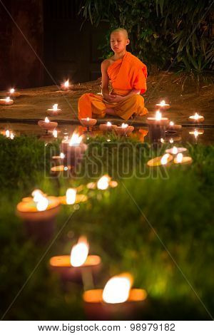 Chiang Mai, Thailand - November 6, 2014: Buddhist monk meditating during Loy Kratong Festival, on November 6, 2014 in Phan Tao Temple, Chiangmai, Thailand.