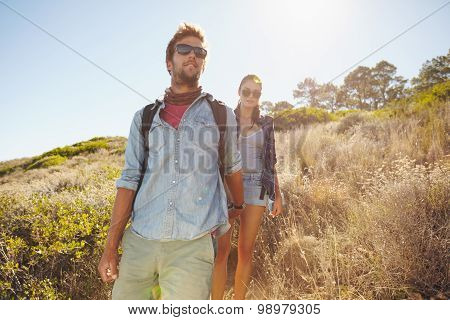 Young Man And Woman Hiking In Mountain