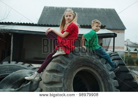 children playing in junkyard tires