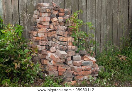 Stack Of Old Bricks On The Fence Background