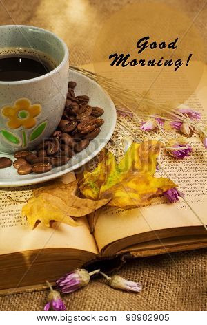 The Cup Of Coffee Lying Ot The Opened Book With Maple Leaves