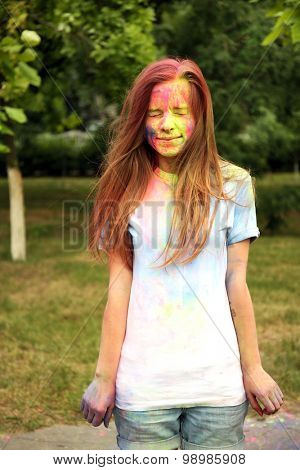 Young woman on Holi color festival in park