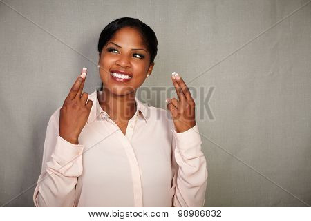 Young Businesswoman Crossing Fingers While Smiling