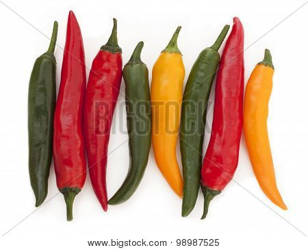 Bright red, yellow and green chili peppers on a white background