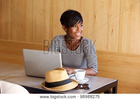 Young Black Woman Smiling And Using Laptop