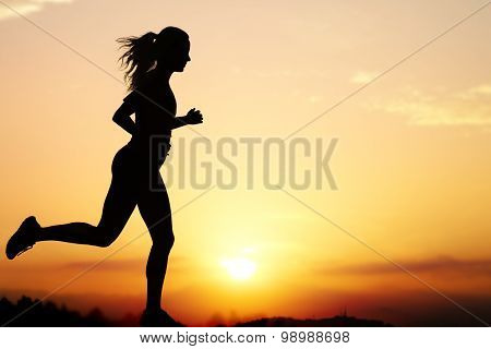 Silhouette Of Female Jogger At Sunset.