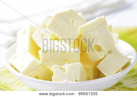 detail of feta cheese cubes in white bowl