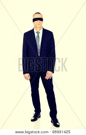 Full length businessman with band on eyes.