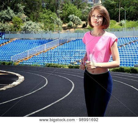 Young woman jogging on stadium