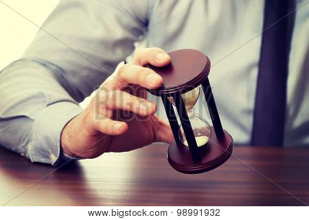 Businessman holding hourglass in the office.