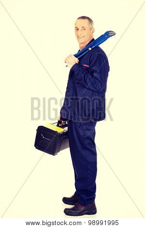 Smiling mature worker with tools bag and wrench.