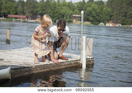 Young Girl Feeds Fish From A Dock In Minnesota With Her Father