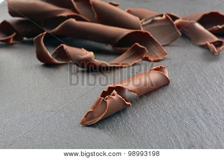 Chocolate curls on wooden table close up