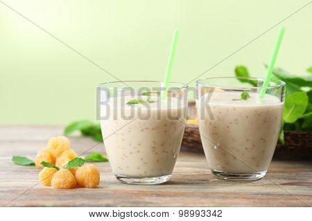 Glasses of raspberry smoothie on wooden table on light background