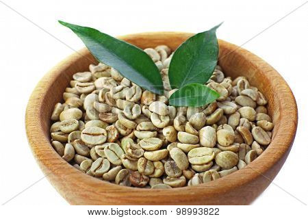 Green coffee beans with leaves in bowl close up