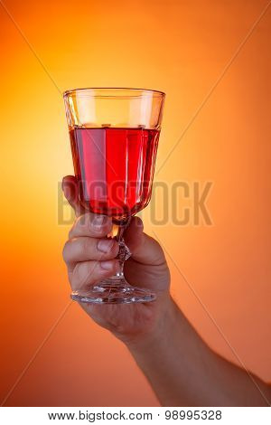 Male Hand Holding A Home Wine Glass Over Abstract Sunset Background