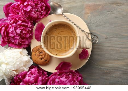 Composition with cup of coffee and peony flowers on wooden background