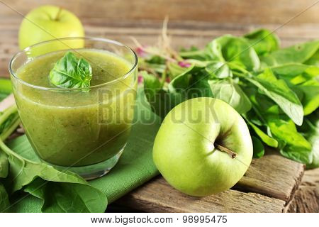 Glass of green healthy juice with spinach and apple on table close up