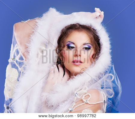 model with bright party makeup against blue background, winter topic