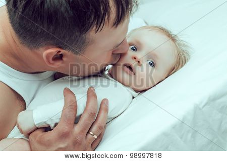 father kissing his two months old baby, in bed at home