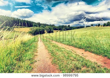 Summer Landscape With Country Road And Wind Turbines