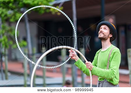 Angler on the street is playing with colorful rings. Auckland city, New Zealand.