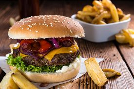 stock photo of burger  - Big fresh made Burger on rustic wooden background  - JPG