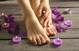 pic of pedicure  - Female feet at spa pedicure procedure with flowers and candlelight on wooden background - JPG
