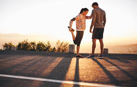 stock photo of jogger  - Outdoor shot of fit young joggers stretching before a run together in morning - JPG