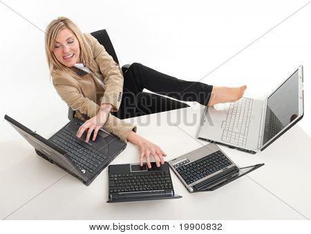 Mujeres jóvenes en un escritorio atestado con ordenadores con manos y pies