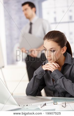 Young attractive woman sitting in office at desk, looking at laptop, man standing in background.?