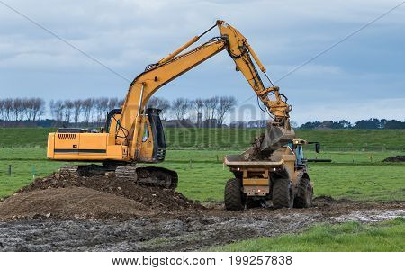 Digger and a tip truck transporting gravel across a muddy Paddock.