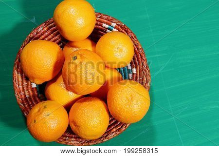 A basket of small oranges on wooden background