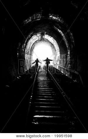 Man And Woman Going Towards The Light, On Railway Tracks