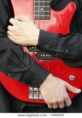 Man Embracing A Red Bass Guitar
