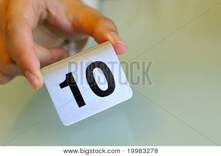 Hand Holding Number Tag